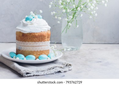 Easter cake kulich. Traditional Easter sweet bread decorated meringue and blue candy cane shape eggs on plate on gray stone table background. Copy space.