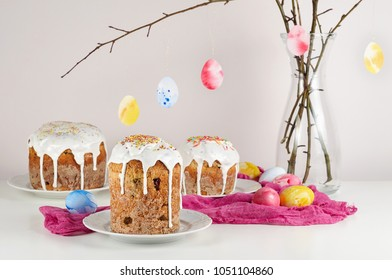 Easter cake on plate, branches of willow decorated painted eggs on a white table with fuchsia gauze napkins. Traditional orthodox christian easter food kulich with raisins