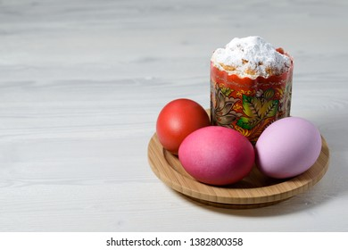 Easter cake and painted eggs on a wooden plate