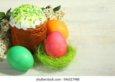 Easter cake and painted eggs on a white wooden background