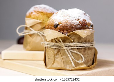 Easter cake panetone close up image with powdered sugar on wooden background. Easter orthodox sweet bread