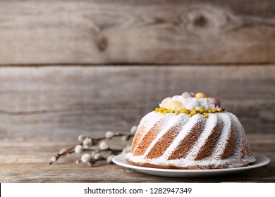 Easter cake in plate with tree branches on grey wooden table
