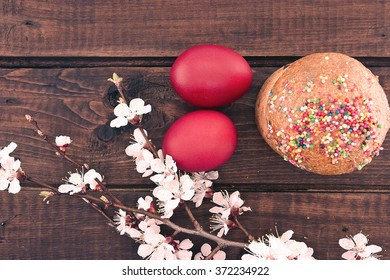 Easter cake and red eggs on rustic wooden table. Top view.