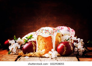 Easter cake and red painted eggs, white apricot flowers, festive composition in rustic style, russian orthodox tradition, vintage wooden background, selective focus