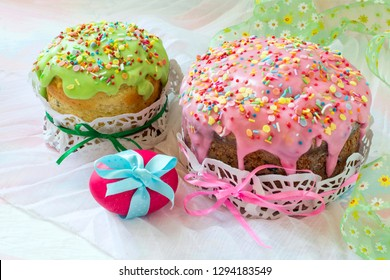 Easter cakes with icing sugar and colorful painted egg on table. Traditional Easter treats of Russia and Ukraine for Orthodox Easter. Bright Easter composition