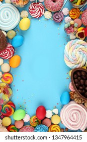 easter candies with jelly and sugar. colorful array of different childs sweets and treats on blue background with eggs