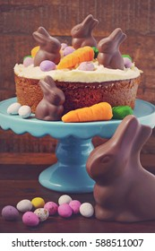 Easter Carrot Cake decorated with mini fondant carrots and chocolate bunnies on dark wood background, with applied retro style filters.