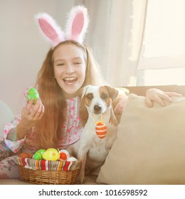 Easter celebration. Child is holding a basket with Easter eggs. Girl with dog