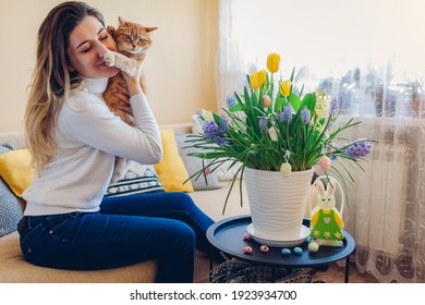 Easter celebration at home. Happy woman hugs cat relaxing on couch. Spring flowers in pot decorated with eggs and bunny on coffee table.
