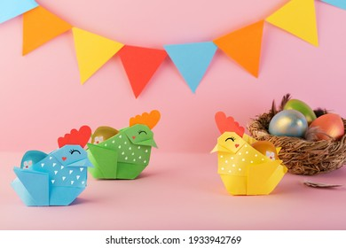 Easter chickens made of paper, handmade. Origami paper egg basket for Easter greetings. Preparation paper crafts for the Easter holiday. Hobbies at home. Self-employment and needlework. DIY concept.