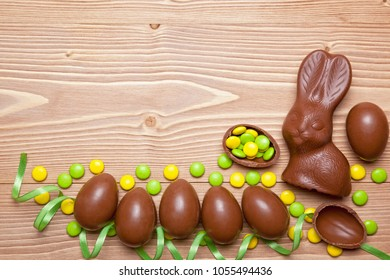 Easter chocolate eggs, bunny and candies on wooden background.