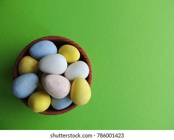 Easter chocolate eggs on bright green background. Different colors.