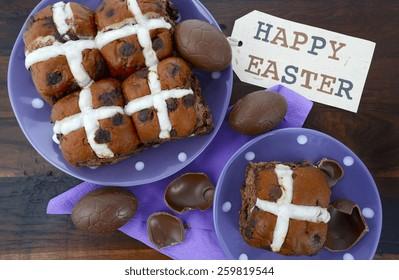 Easter chocolate hot cross buns on dark wood table.
