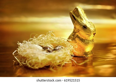 Easter chocolate rabbit and nest with chocolate eggs over gold background