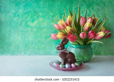Easter chocolate rabbit, spring flowers and colorful eggs