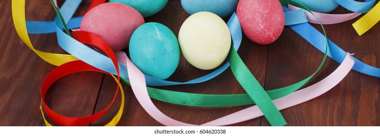 Easter. Close-up of Easter eggs and multicolored ribbon on a wooden table.
