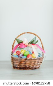 Easter color eggs in festive gift basket, light gray wooden background with copy-space