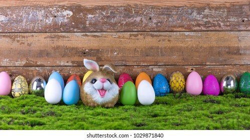 Easter, colored Easter eggs and a rabbit on the grass