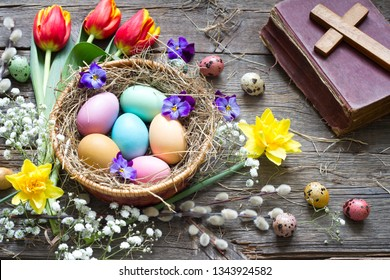 Easter colorful eggs in the nest with flowers on vintage wooden boards with bible and cross