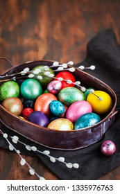 Easter colorful painted eggs and willow on dark rustic background, spring holiday concept