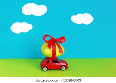 Easter is coming, little red toy car with a colored easter egg tied on its roof driving through a green landscape with blue sky and clouds