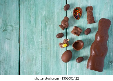 Easter composition with chocolate eggs and animals on wooden surface