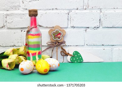 Easter. Easter composition with colored painted eggs, flowers. Glass bottle with colored sand. The white brick wall. Mint, green and white background. happy Easter. Place for text.