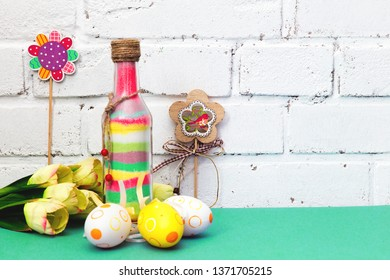 Easter. Easter composition with colored painted eggs, flowers. Glass bottle with colored sand. The white brick wall. Mint, green and white background. happy Easter. Place for text