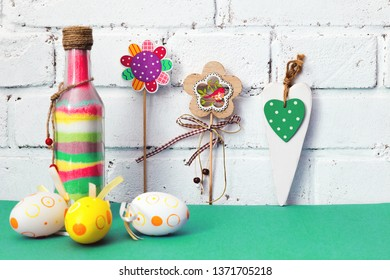 Easter. Easter composition with colored painted eggs, flowers. Glass bottle with colored sand. The white brick wall. Mint, green and white background. happy Easter.