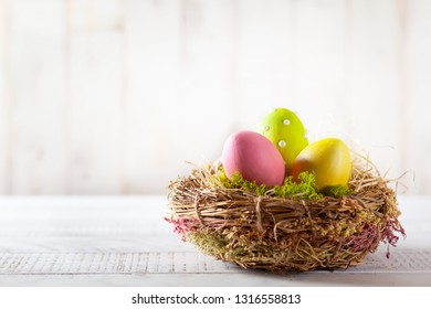 Easter composition with colorful Easter eggs in nest on wooden background. Easter card with copy space.