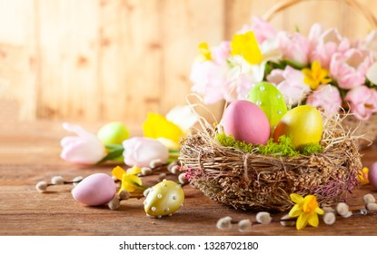 Easter composition with colorful Easter eggs in nest ,spring flowers and branches of pussy willows on wooden background. Easter card with copy space.