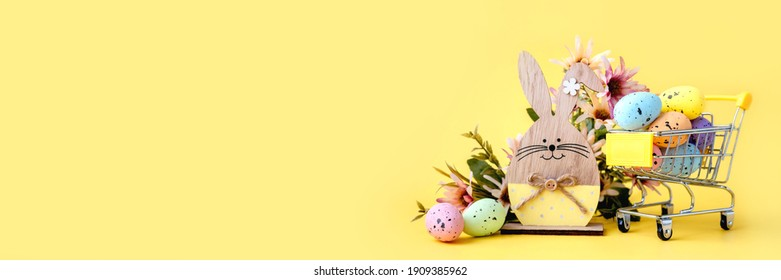 Easter composition with colorful eggs in shopping cart, wooden bunny and spring flowers on yellow background. Banner. Copy space