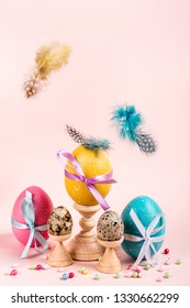 Easter composition with decorated eggs and flying feathers.