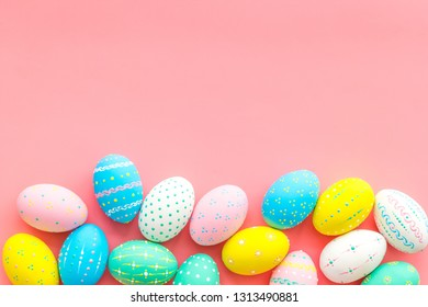 Easter composition. Decorated pastel Easter eggs on pink background top view space for text