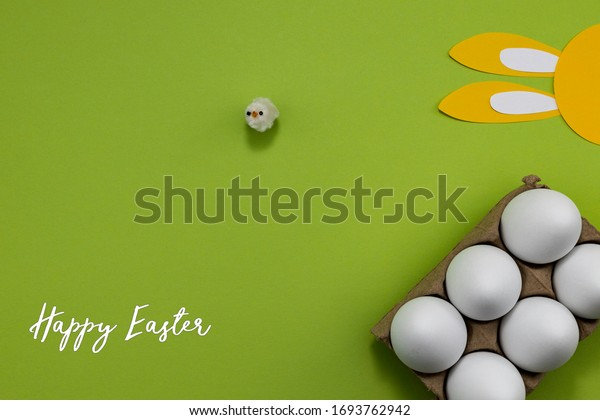 Easter composition with an egg carton, a toy baby chicken and paper bunny ears. On a green background with room for copy.