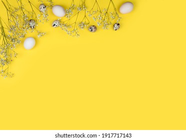 Easter composition. Easter eggs, flowers, paper blank on yellow background. Flat lay, top view, copy space, mock up. High quality photo