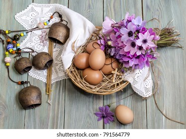 The easter composition. Eggs in a wicker basket, a bouquet of wild anemones and  church candles on wooden table close-up.