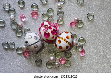 Easter composition flatlay. Easter eggs are decorated with shiny rhinestones on a silver background with glass ornaments and pearl beads.