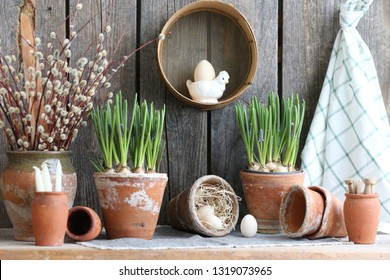 Easter composition with hyacinth in old clay aged pot, wooden eggs on straw, branches of willow in vase, vintage authentic primitive rustic decor with porcelain chicken figurine on wooden background