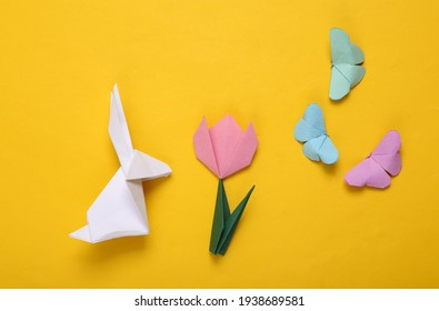 Easter composition of origami tulips, rabbit and butterflies, eggs on a yellow background