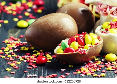 Easter composition: rabbit, chocolate eggs and sweets, red tulips and colorful sugar, selective focus