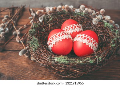 Easter composition of red Easter eggs, nest and willow branches.