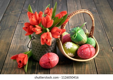 Easter composition with red tulips and a basket of colored Easter eggs on dark rustic wooden table