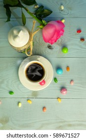 Easter composition. Rose, a jar with Easter Bunny, a cup of coffee, candy.