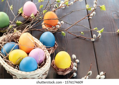 Easter composition - several colored eggs in a basket and on a dark wooden table with willow twigs, place for text, copy space