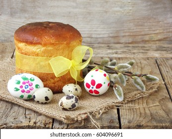 Easter composition of sweet bread, paska, willow twigs and eggs on light wooden background. Orthodox kulich. Holidays breakfast concept with space for text.