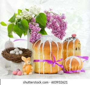 Easter composition with traditional Russian Easter bread kulich, Easter eggs and lilac flowers on table