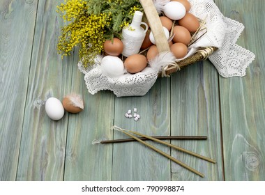 Easter composition. Wicker basket with eggs, branches of mimosa, holy water, church candles and incense on a wooden background close-up.