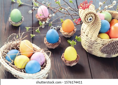 Easter composition - a wicker basket in the form of a chicken with colored eggs on a dark wooden table with willow twigs