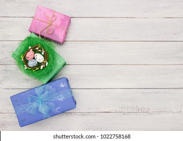 Easter concept- easter colored eggs in the nest , gift boxes  on white wooden background.Greeting card template